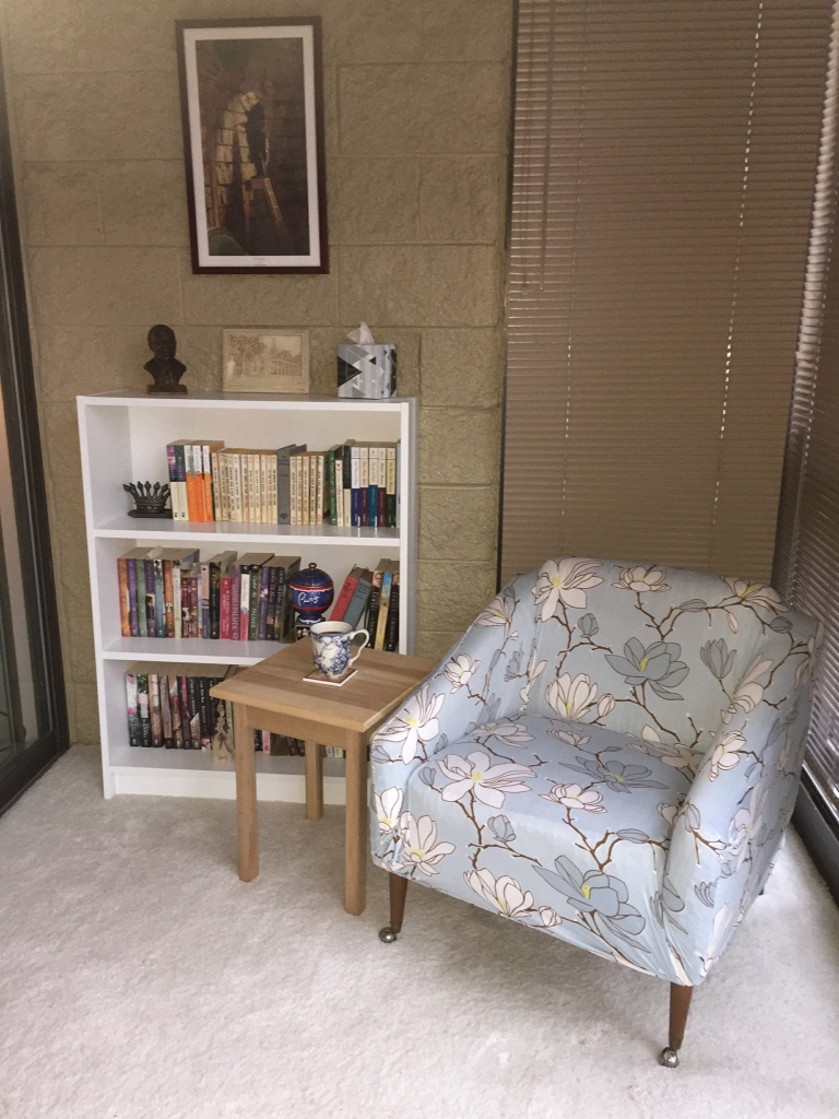 Photo of chair, side table with coffee mug, and short bookcase with books on each shelf.