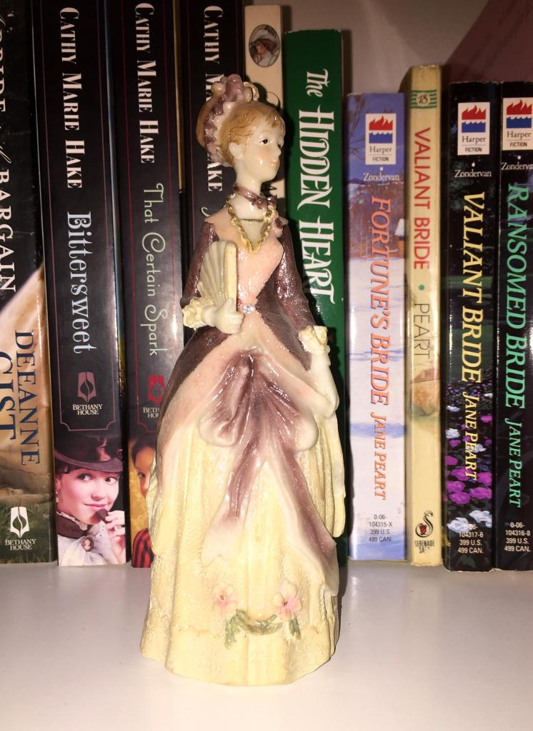 Photo of porcelain figurine of woman dressed in 19th century gown.